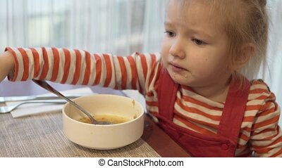 The little girl eats vegetable soup. She sits at the table and holds a spoonful of soup