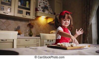 The little girl in the kitchen playing with dough and flour,...