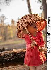 The little girl in the woods with a basket stands on a beautiful maple leaves a lot