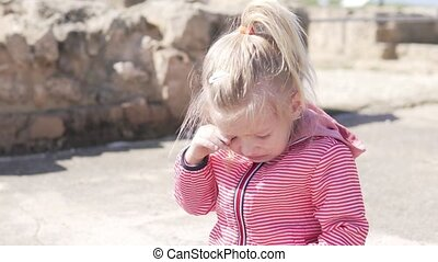 The little girl is crying. A child on the street in a jacket roars