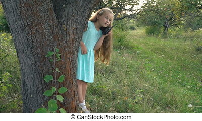 little girl is playing with a walkie-talkie outdoors