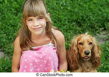 The little girl is sitting in the grass with dog