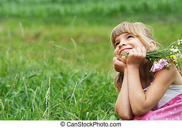 The little girl is sitting in the meadow