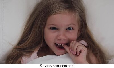 The little girl is staggered by a milk tooth. The tooth is...