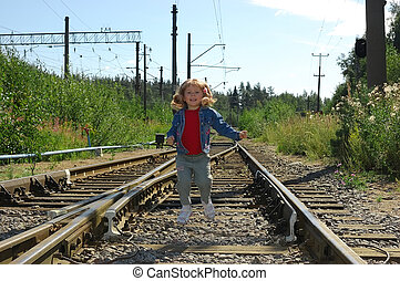 The little girl jumping on railway rails