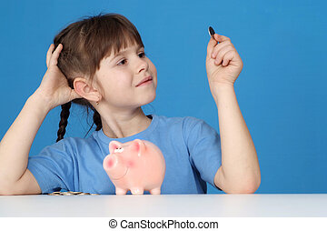 The little girl looks at a penny