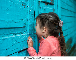 the little girl looks at an old door