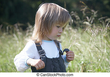 The little girl on a background of meadow