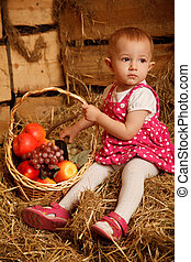 The little girl on straw with a basket of fruit against the wall of boards. Vertical format.