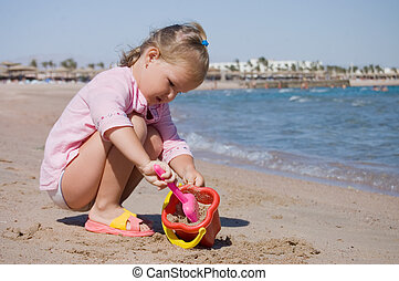 The little girl plays on seacoast