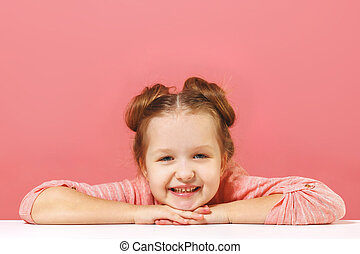 The little girl sits at the table, puts her head in her arms. Pink background. Copy space. Close-up.