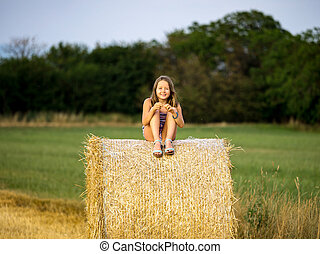 The little girl sits on a haystack in the twilight of day