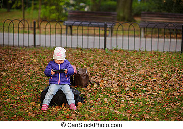 The little girl sits on a lawn in autumn park.