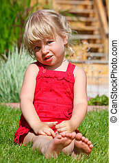 The little girl sits on a lawn