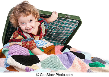 The little girl sitting on a suitcase