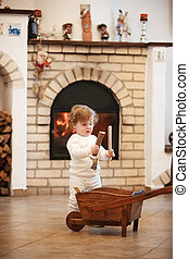 The little girl standing at home against fireplace