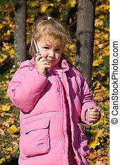 The little girl talks on a cellular telephone
