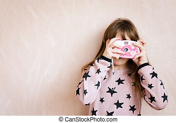 The little girl with a pink photo camera.