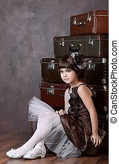 The little girl with old suitcases