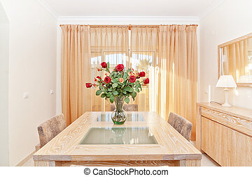 The living room of a beautiful bouquet of red roses in a vase. On the table.