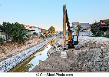 The loader excavator is trying the soil in the canal.