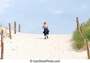 The lonely boy walking through a sand dune