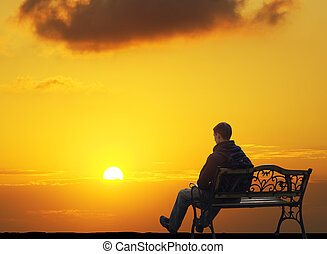 The lonely man sits on a decline.Creative Outdoor Photo.