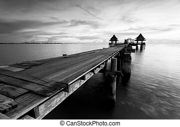 The long bridge over the sea with a beautiful sunrise in black a