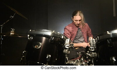 The long-haired drummer finishes playing the drum set in a dark room on a black background. Rock musician. Static plan. Wide angle