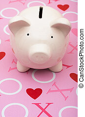 The Love of Money - A piggy bank on a pink love background,...