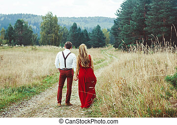 the lovers are standing on a forest road