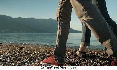 The loving couple walk on the shingle beach near sea in sunny day.