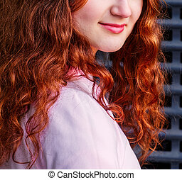The lower part of the face of a cute girl with long red hair.