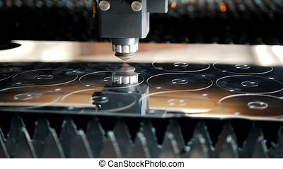 The machine draws smooth circles on the metal sheet, close...