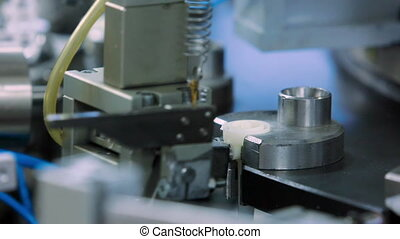 The machine inserts the lid on the production of droppers at the medical equipment factory