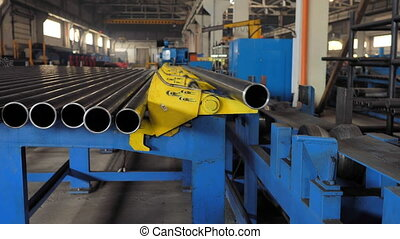The machine loads a metal pipe to the production line. -...