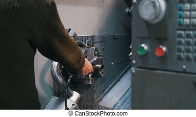The machine operator flushes the lathe with a liquid. Close...