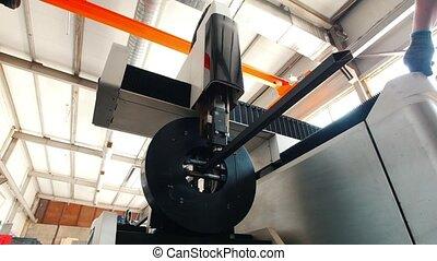 The machine saws metal, a man-worker accompanies this...