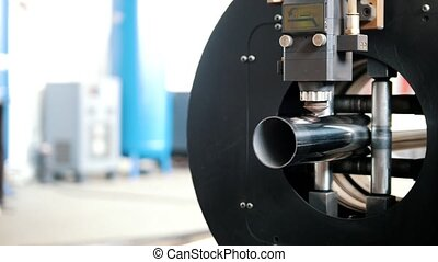 The machine saws metal in the form of a cylinder, close up