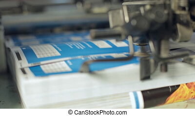 The machine works at the printing house and prints color booklets