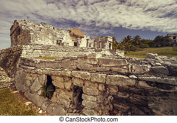 Side view of the remains of a small Mayan temple in the Tulum complex in Mexico taken at sunset.