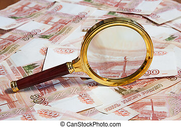 The magnifier lays on the Russian money