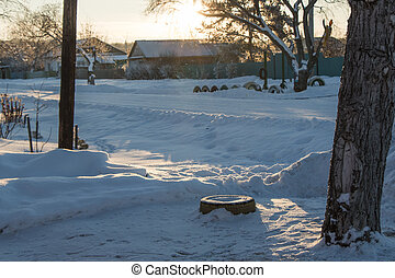 The main street of a Russian village in winter at sunset in freezing weather