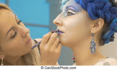 The make-up artist draws the model's lips in purple. Creates a magical image. Preparation for an artistic photo shoot