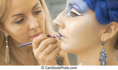The make-up artist paints the lips of the model in purple. She creates a fairy-tale image for an artistic photo session