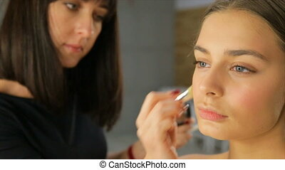 The make-up artist puts on the face of the girl a cream