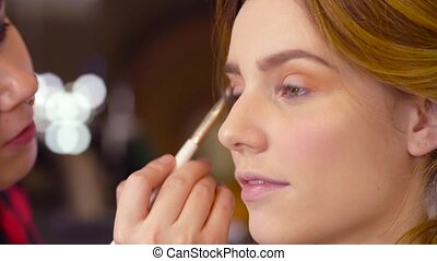 The makeup artist applying eyeshadow - Close up. Portrait of...