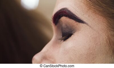 The makeup artist applying eyeshadow on the eyes - Close up....