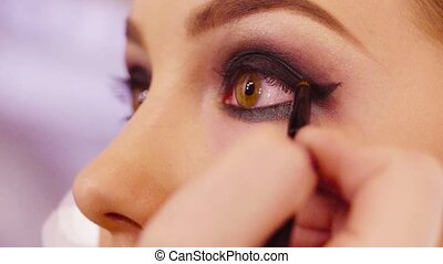 The makeup artist shading eyeshadow - Extreme close up of...