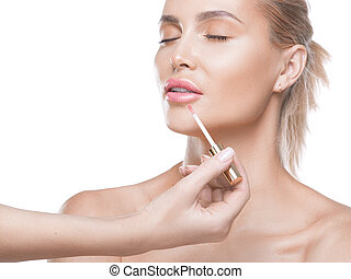 The making of nude look for lips. Fresh and sparkling lips made by a lip gloss and professional lip brush. The finishing accent for every make up.